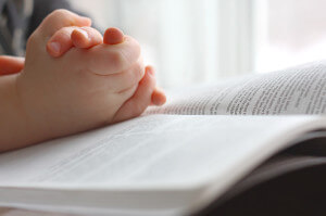 Childs hands on Bible