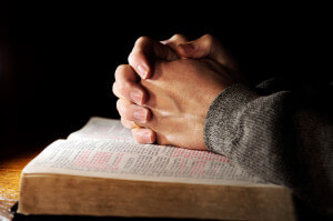 Hands folded on Bible